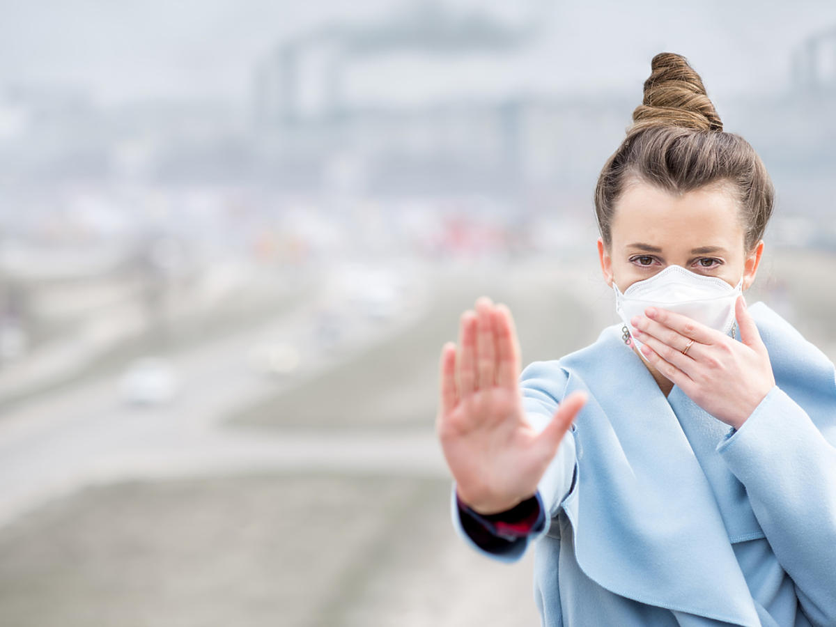 Kobieta w masce ochrania się przed szkodliwym działaniem smogu.