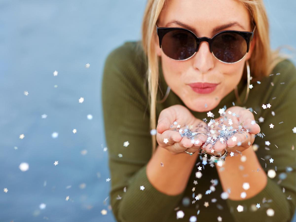 Kobieta w okularach przeciwsłonecznych zdmuchuje brokat z dłoni.