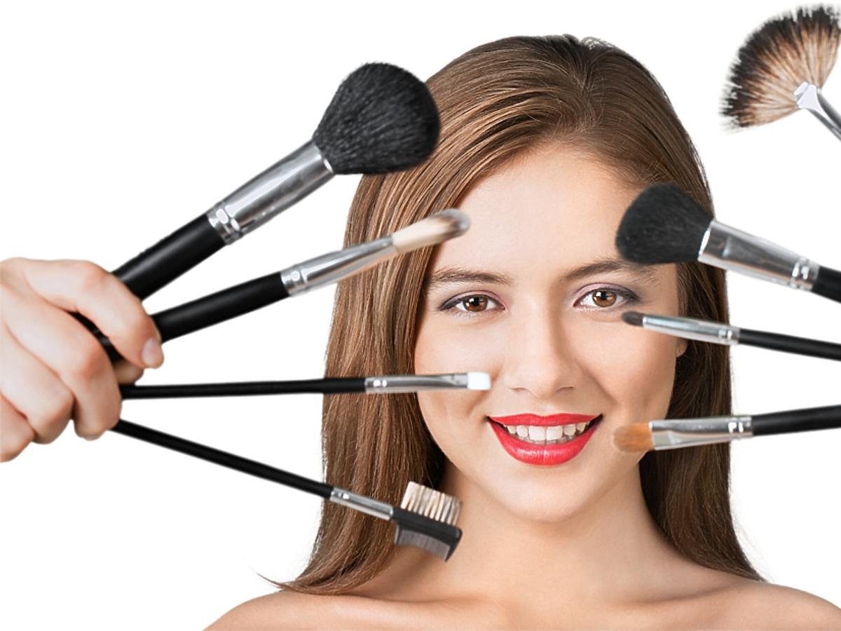 Kobieta w rozpuszczonych włosach z pędzlami do makijażu.