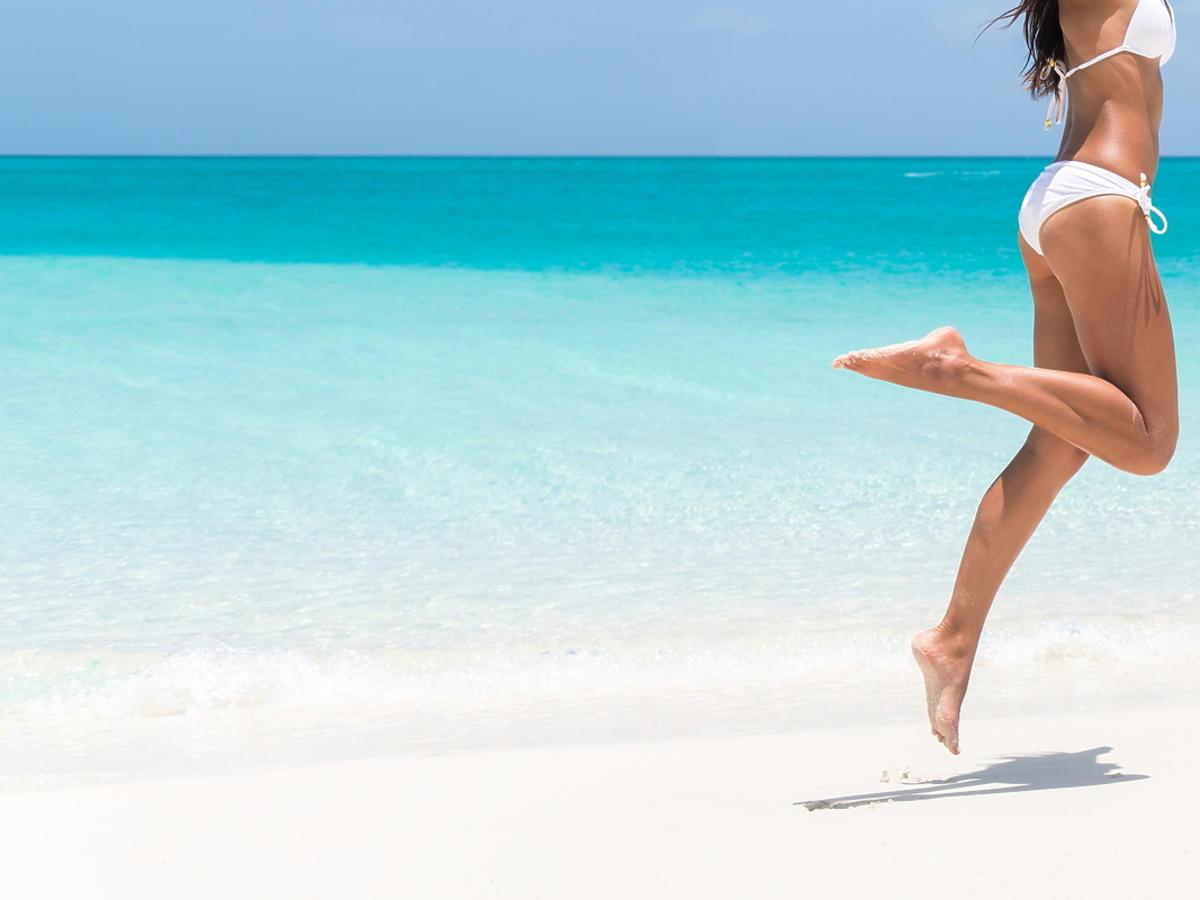 Kobieta w stroju kąpielowym chodzi po plaży.