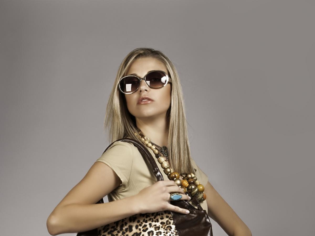 kobieta w stroju w kolorze ecru, z torebką w gepardzie cętki i okularach przeciwsłonecznych