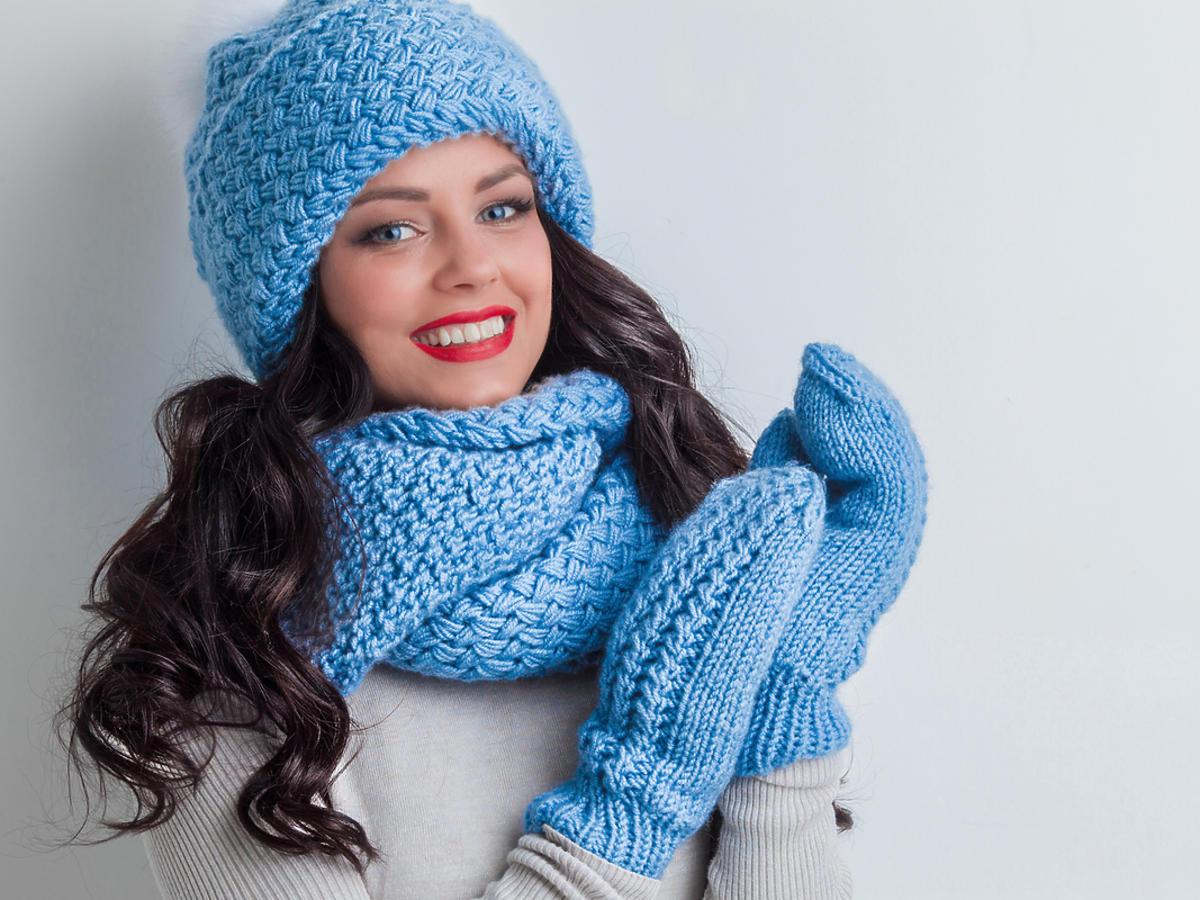 Kobieta w szaliku, czapce i rękawiczkach.