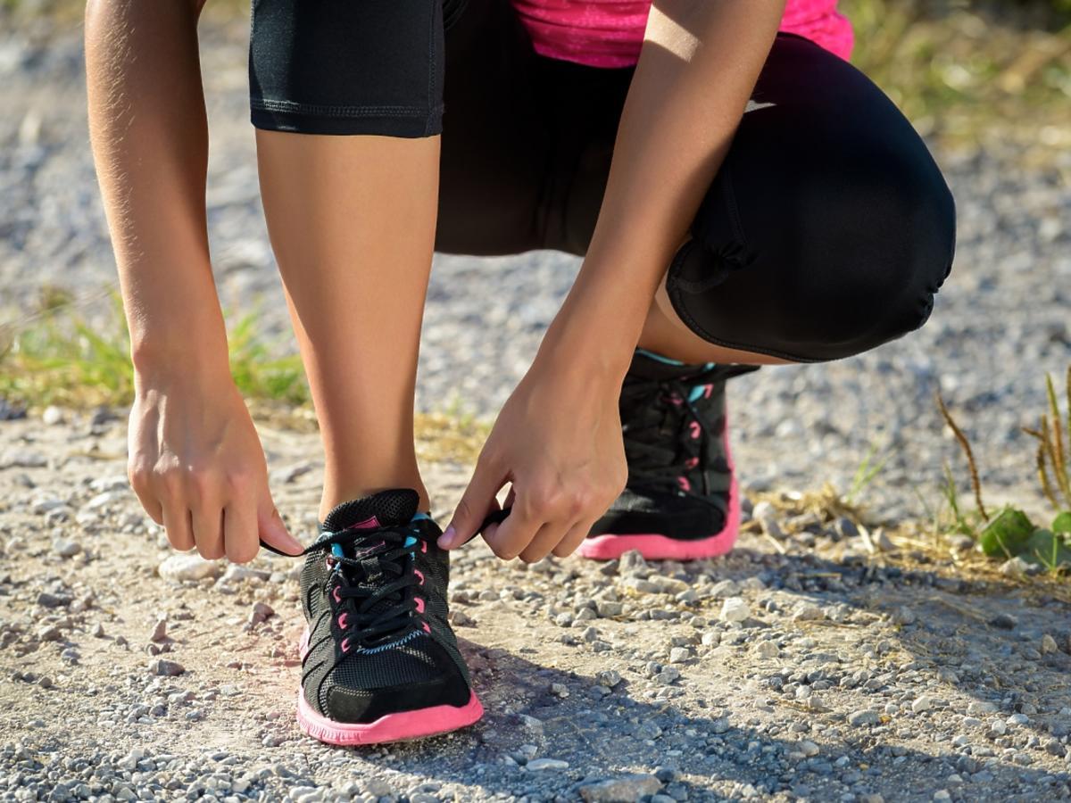 Kobieta wiąże buty sportowe.