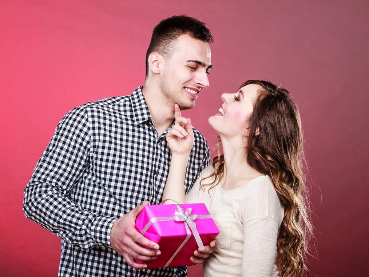 kobieta wręczająca mężczyźnie romantyczny prezent