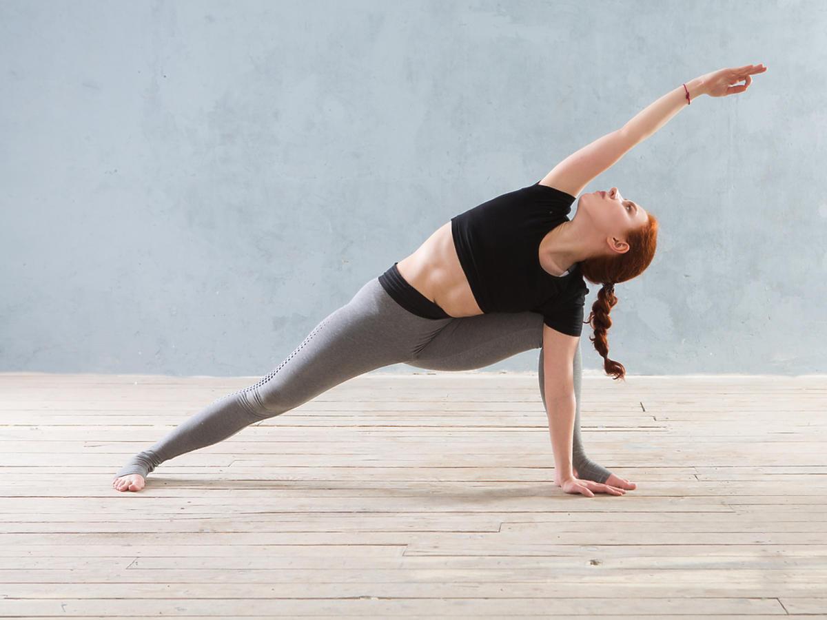 Kobieta wykonująca pozycję jogi w staniu.