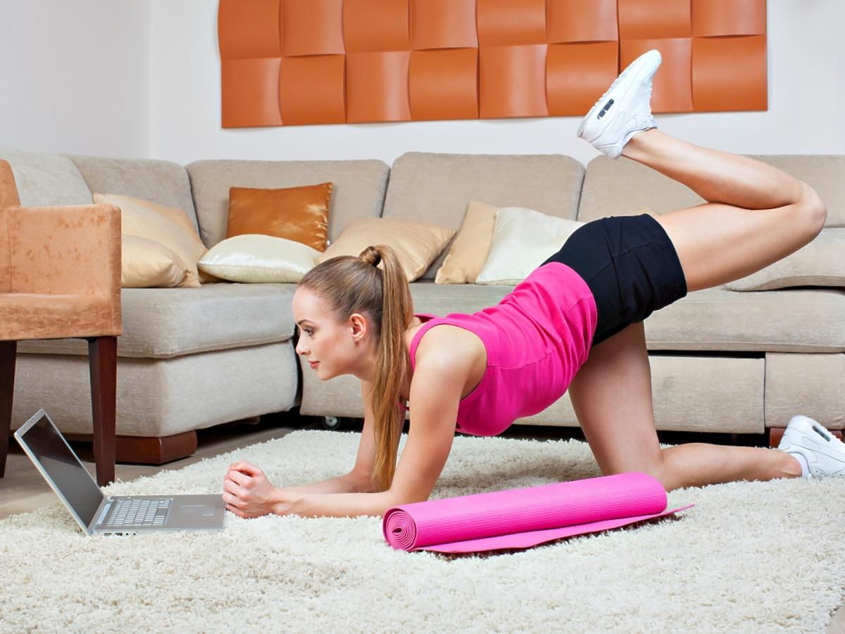Kobieta wykonuje ćwiczenia na masę w domu