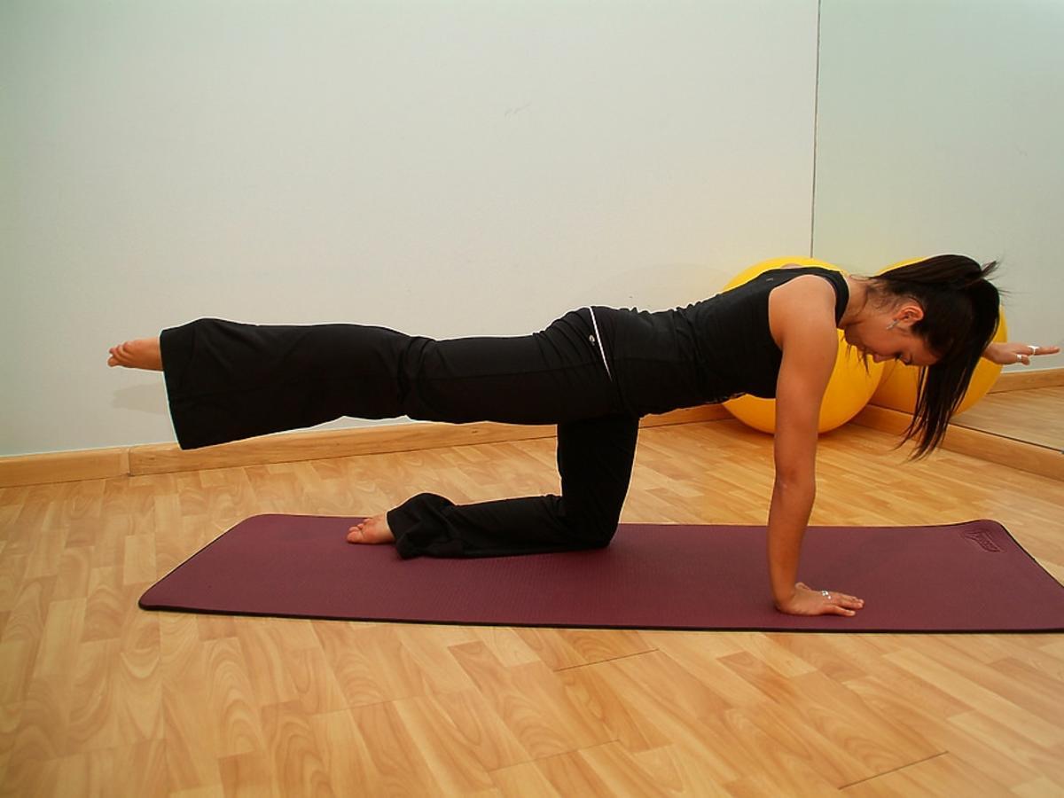 Kobieta wykonuje gimnastykę na macie ćwiczeniowej