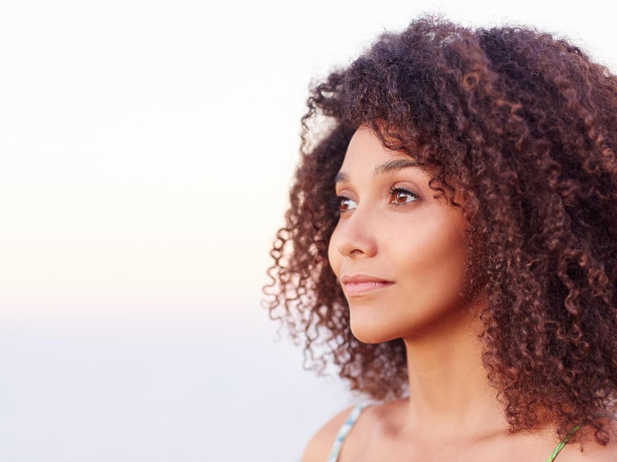Kobieta z ciemnymi, kręconymi włosami patrzy w dal