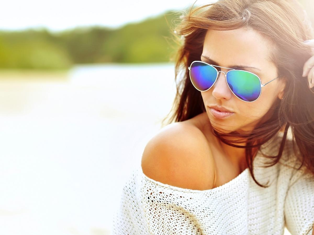 Kobieta z długimi brązowymi włosami siedzi na plaży.