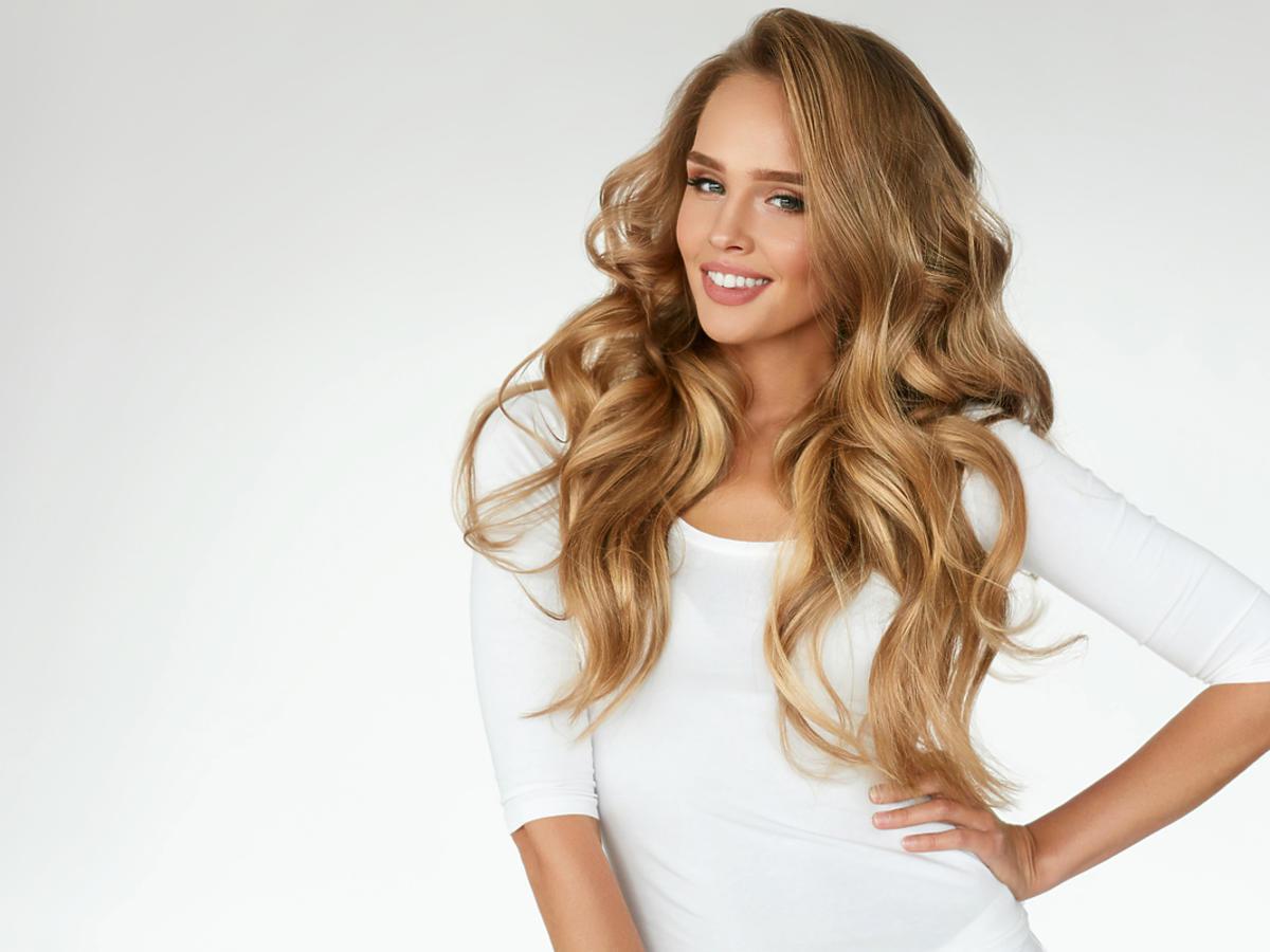 Kobieta z długimi, jasnymi włosami uśmiecha się.