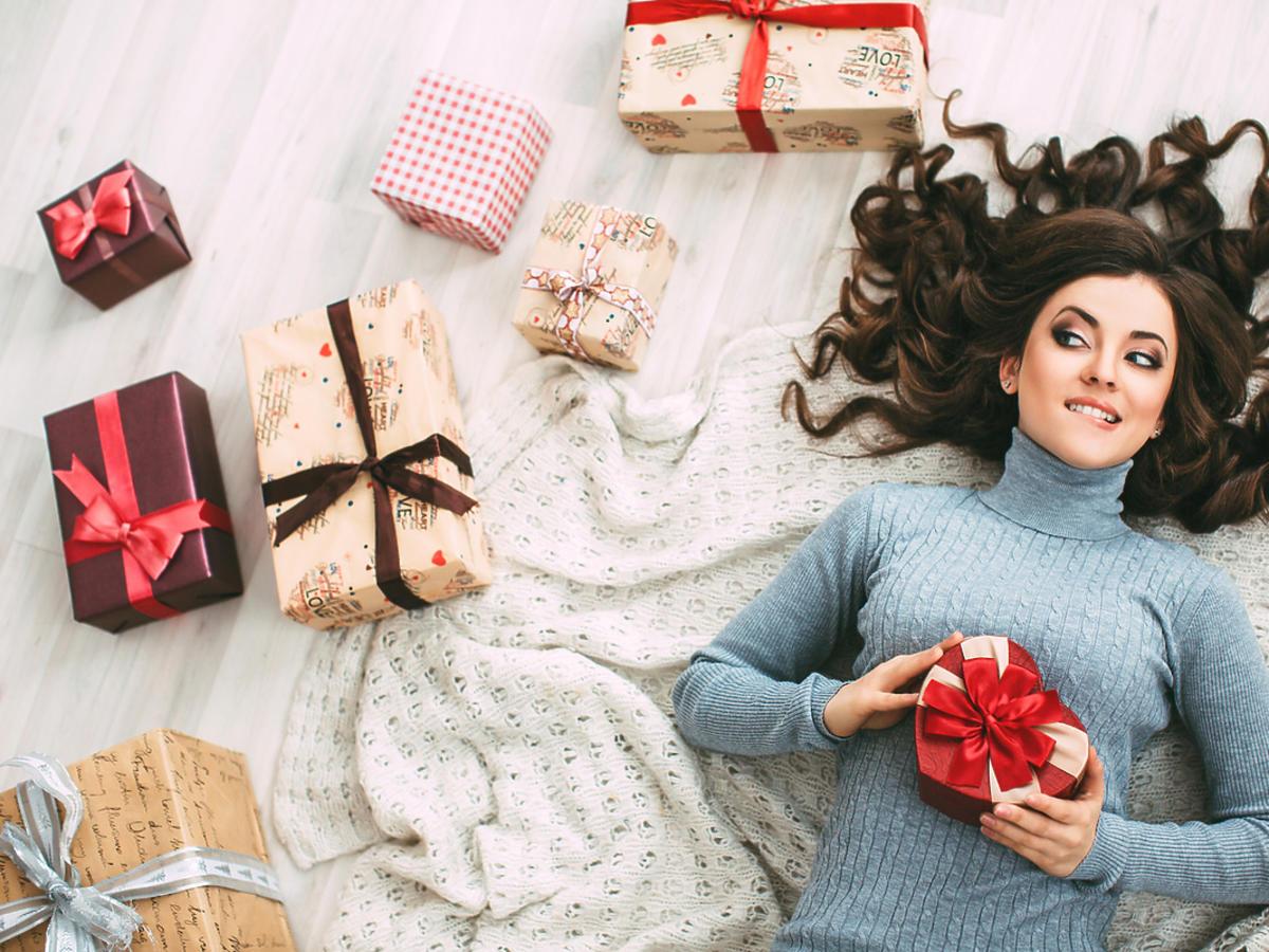 Kobieta z długimi włosami leży na dywanie, obok niej leży kilka prezentów