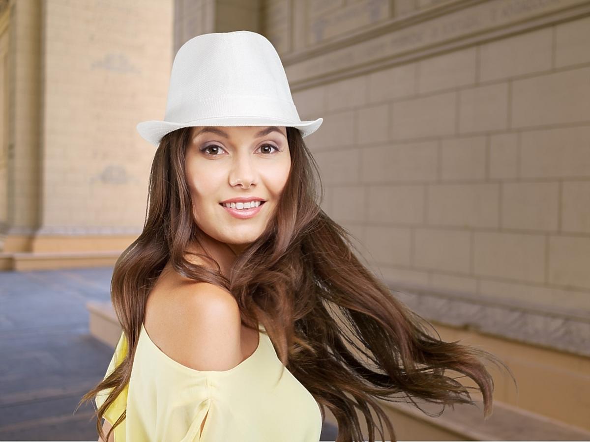 Kobieta z długimi włosami w białym kapeluszu