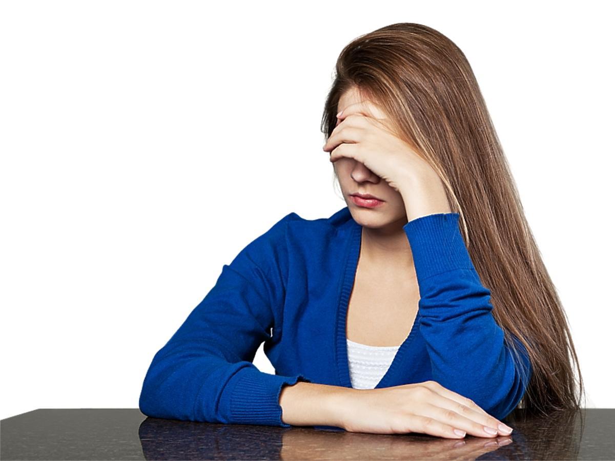 Kobieta z długimi włosami zasłania oczy