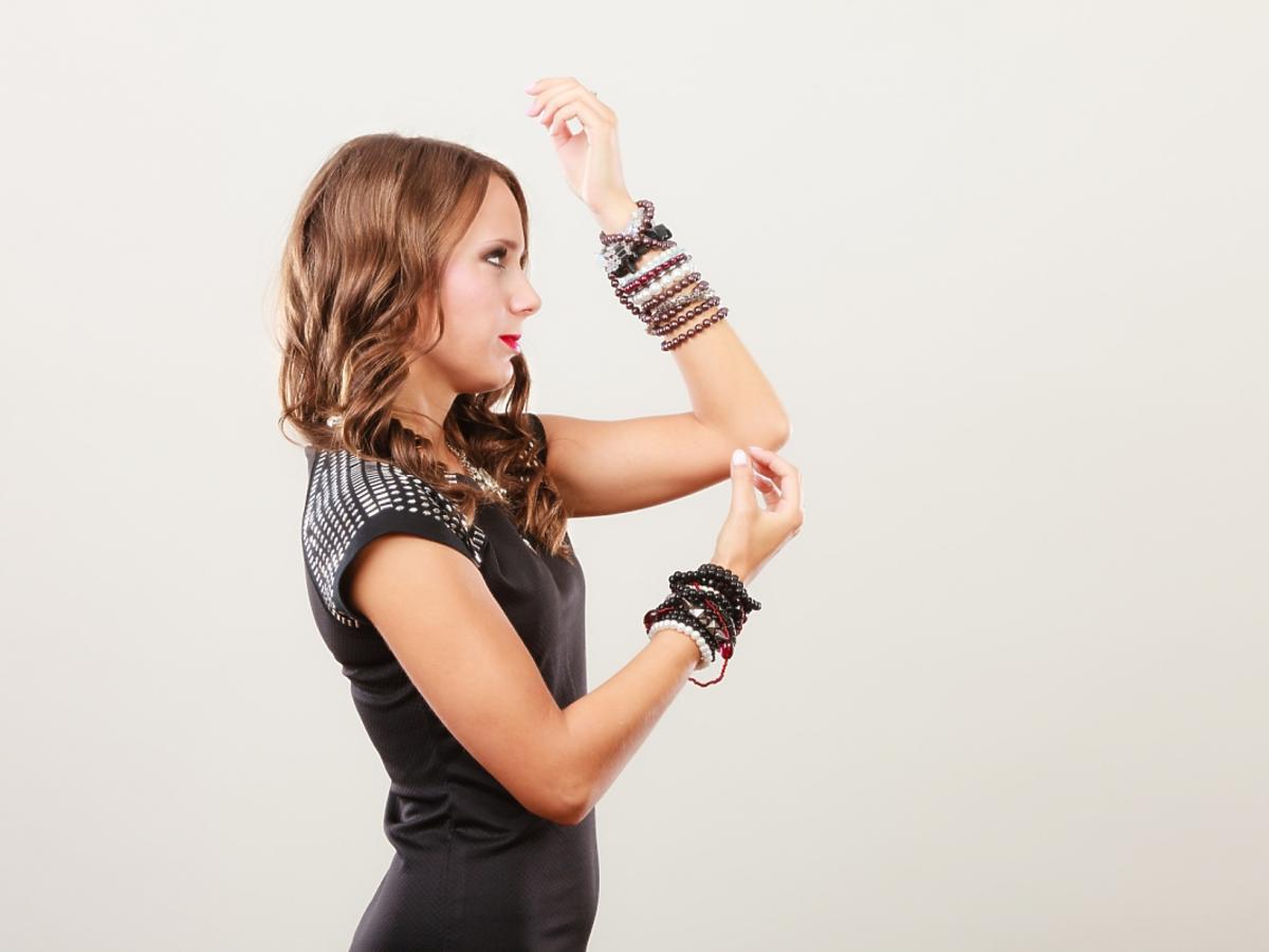 kobieta z dużą ilością bransoletek na obu rękach