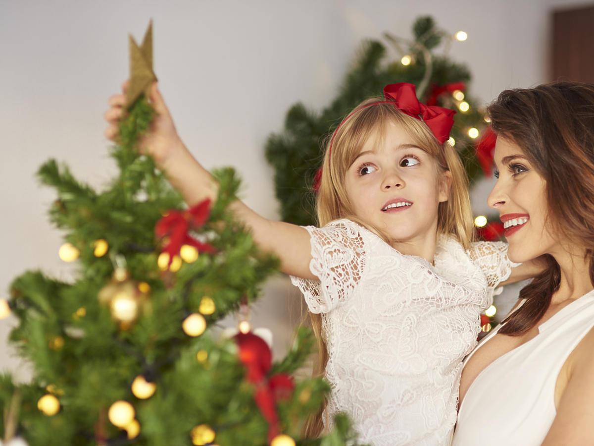 Kobieta z dzieckiem na rękach dekoruje choinkę