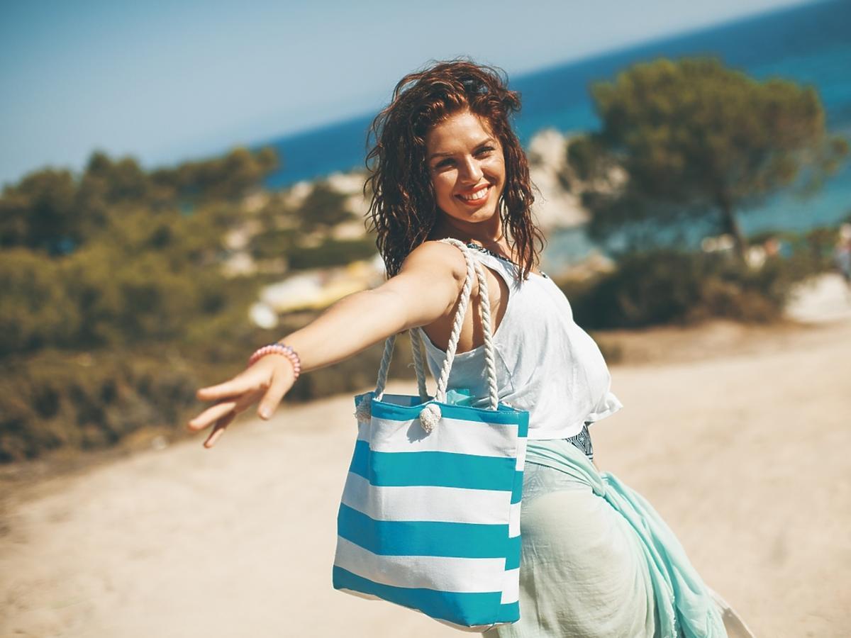 Kobieta z kręconymi włosami spaceruje po plaży z torebką w marynarskie paski.