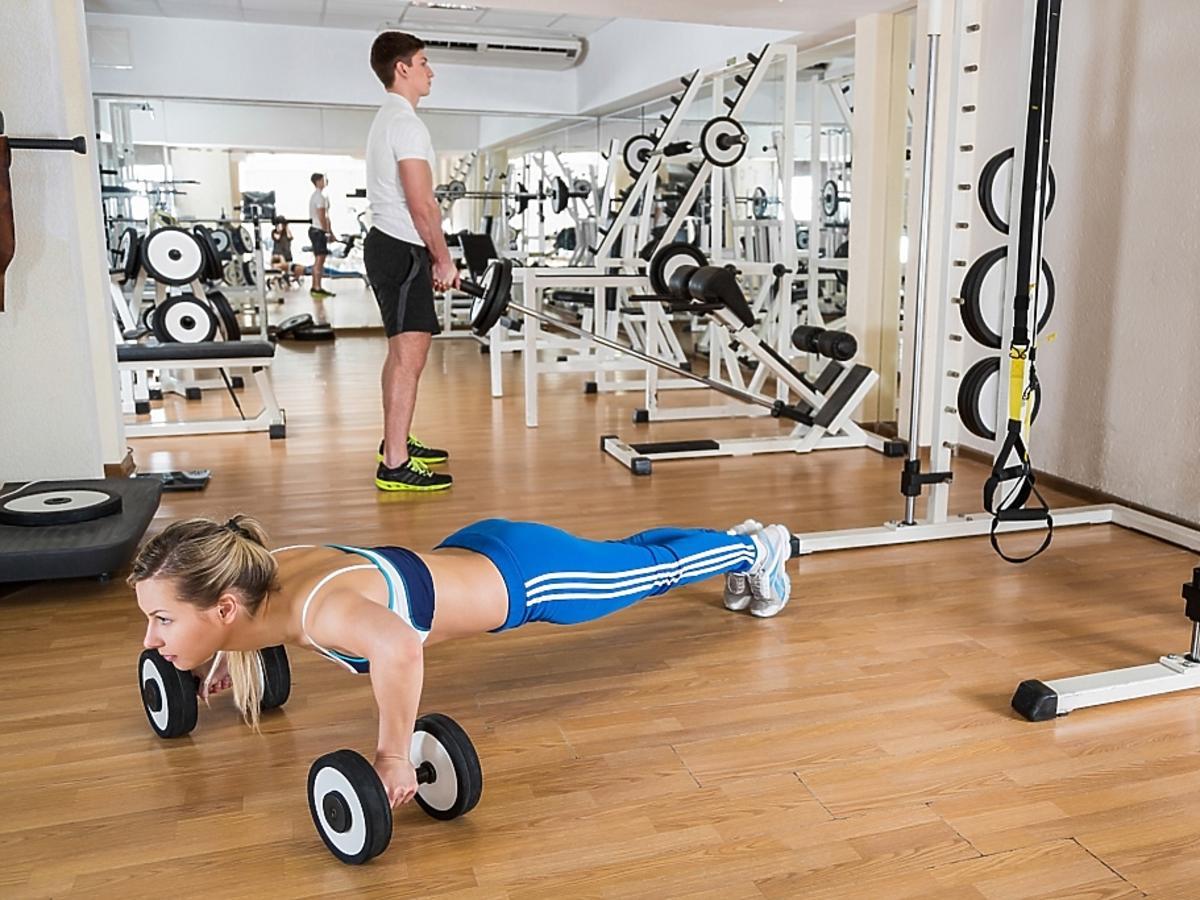 kobieta z mężczyzną trenują na siłowni