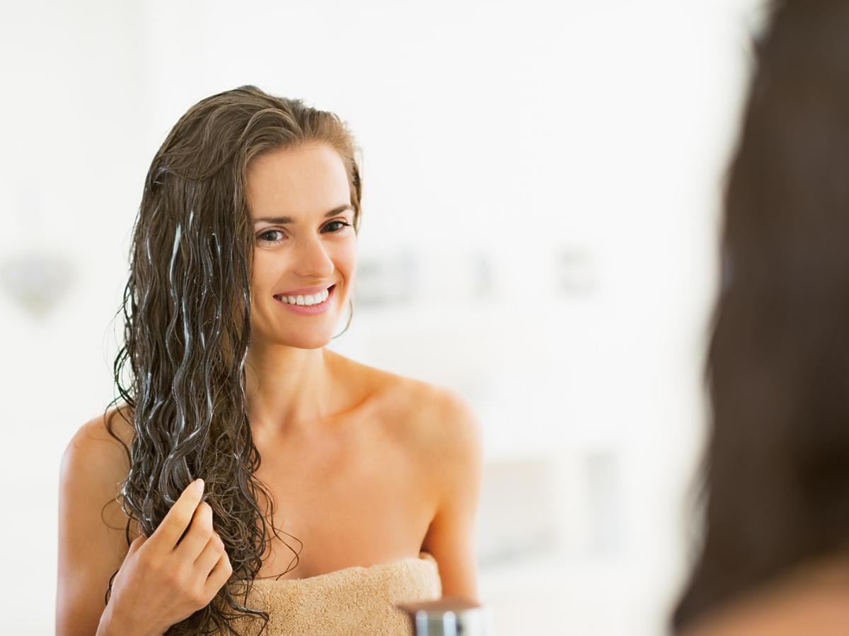 Kobieta z mokrymi włosami w łazience.