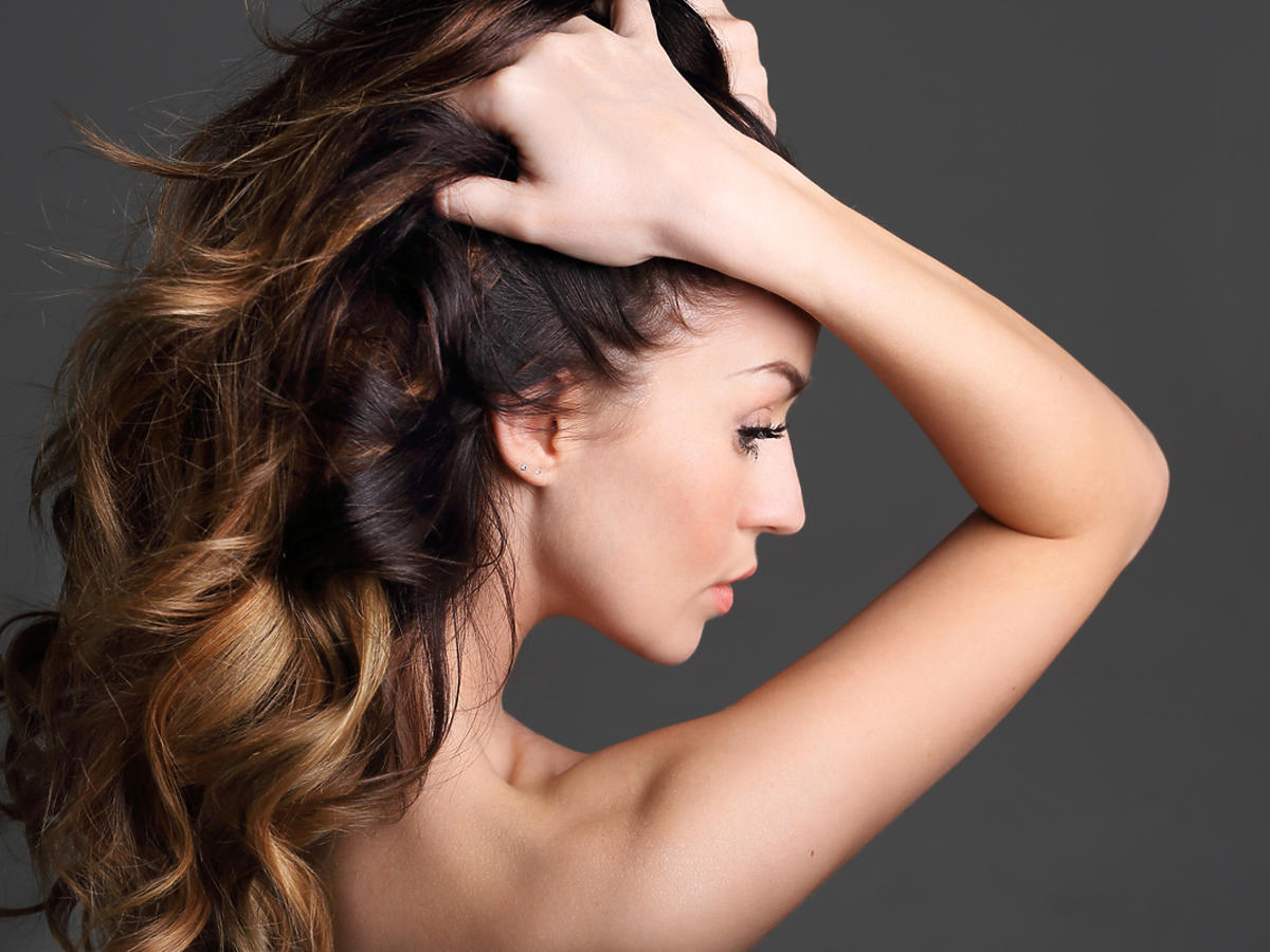 Kobieta z pięknymi, zdrowymi, falowanymi, ciemnymi włosami.