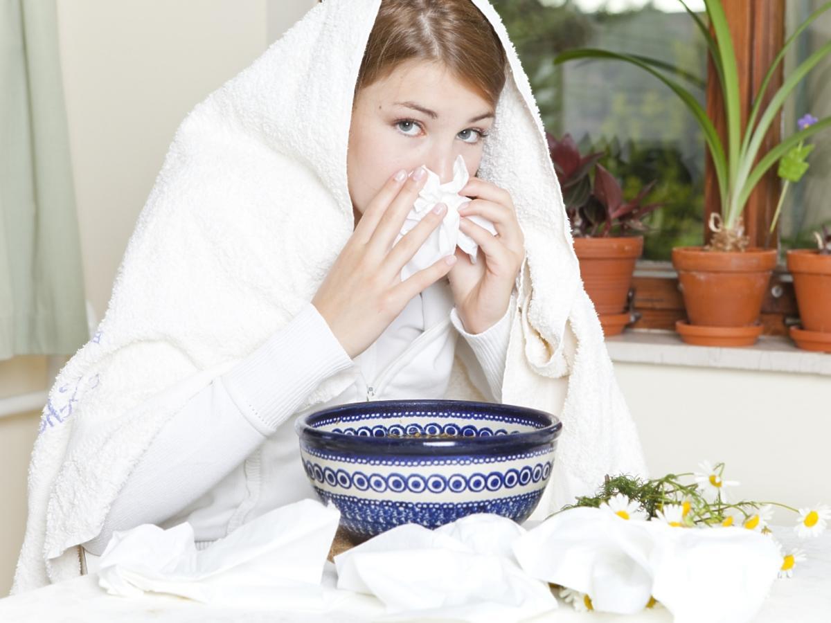 Kobieta z ręcznikiem an głowie robi inhalacje.