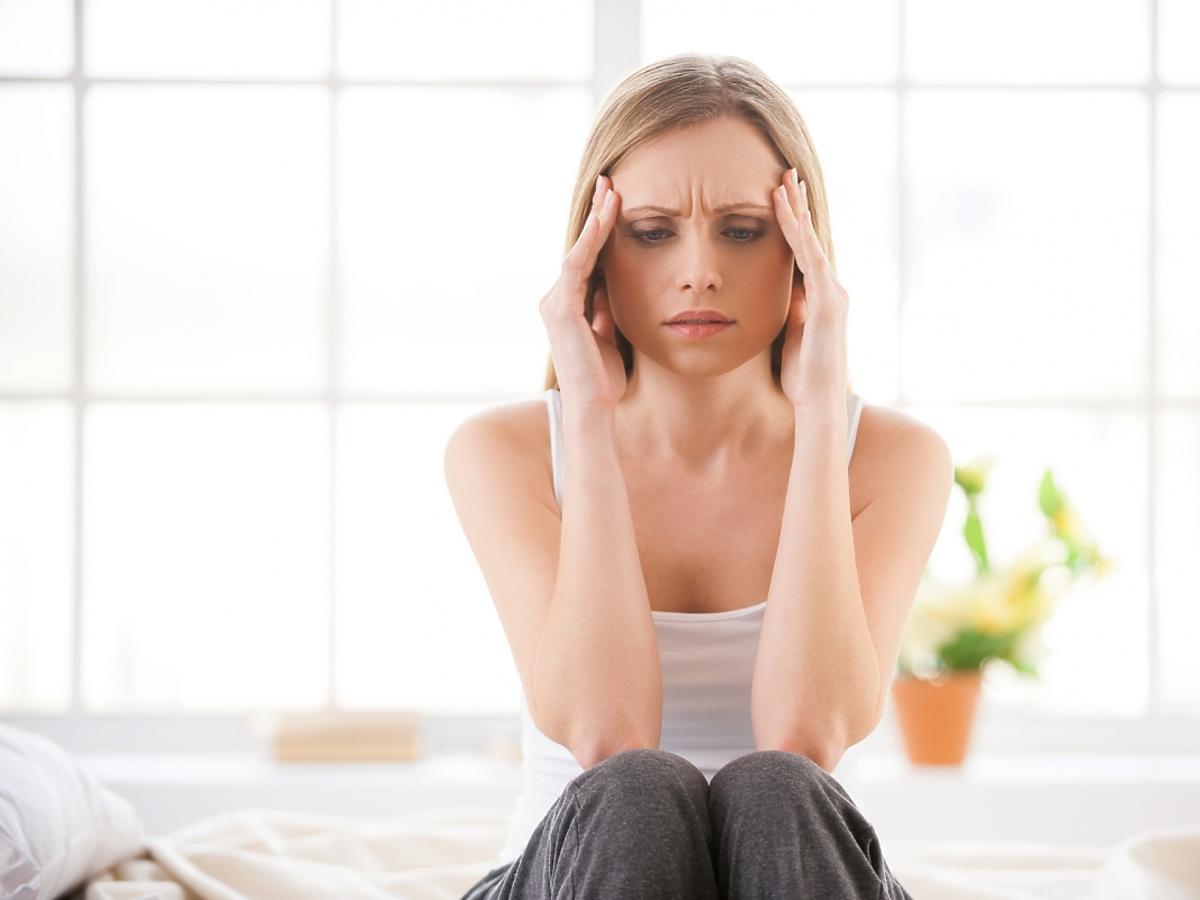 Kobieta z silnym bólem głowy siedzi na łóżku