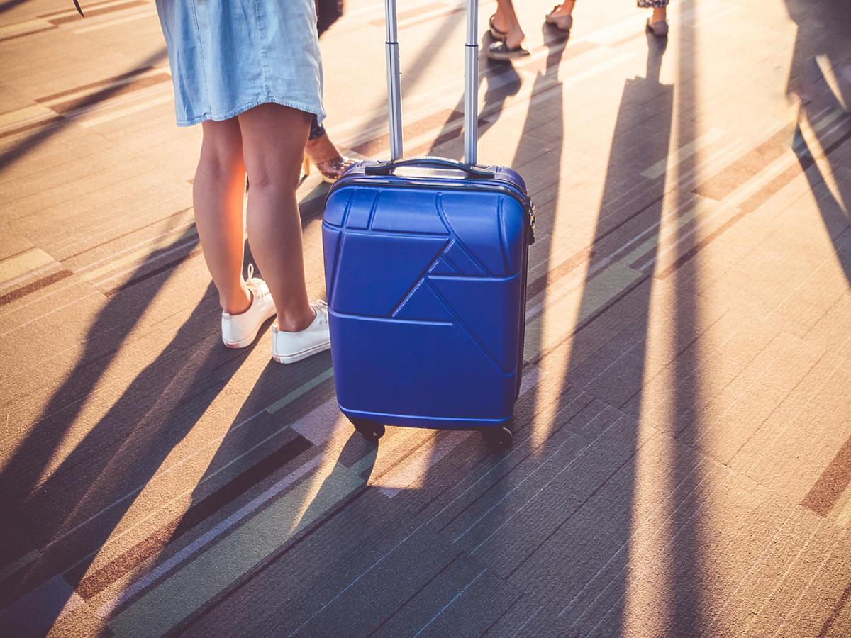 Kobieta z walizką podróżną czeka na samolot na lotnisku.
