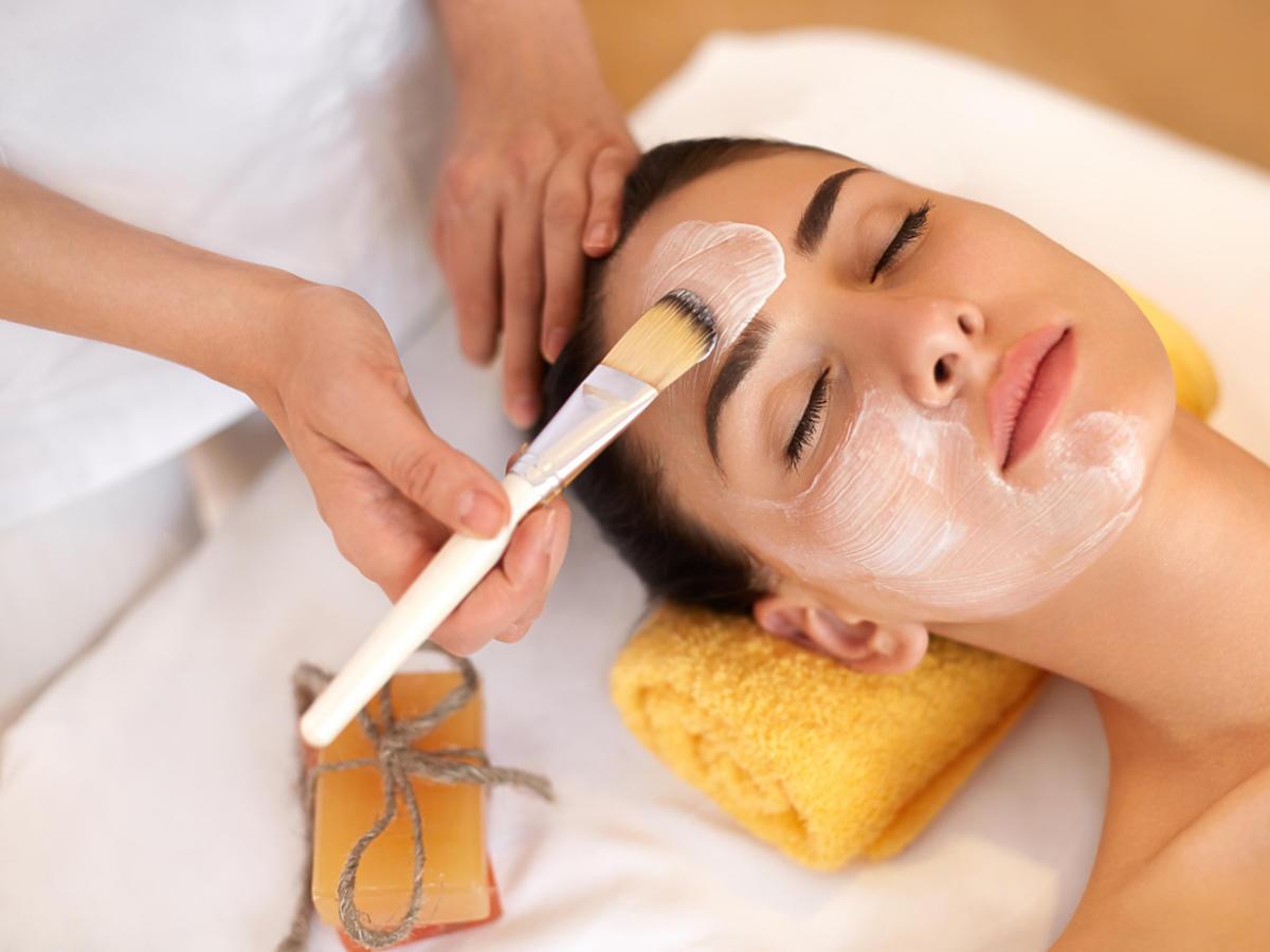 Kobieta z zamkniętymi oczami jest poddawana zabiegom kosmetycznym. Ma na twarz nakładaną maskę.