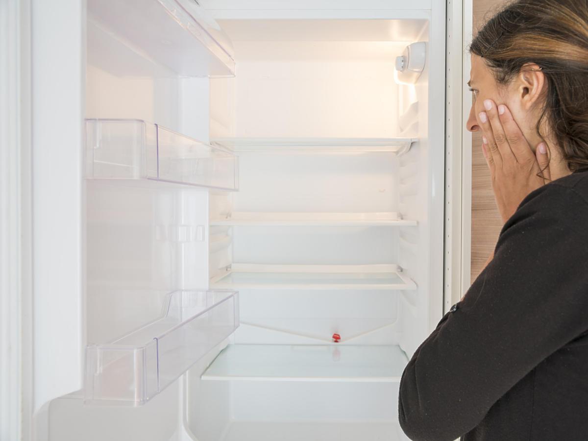 Kobieta zagląda do pustej lodówki