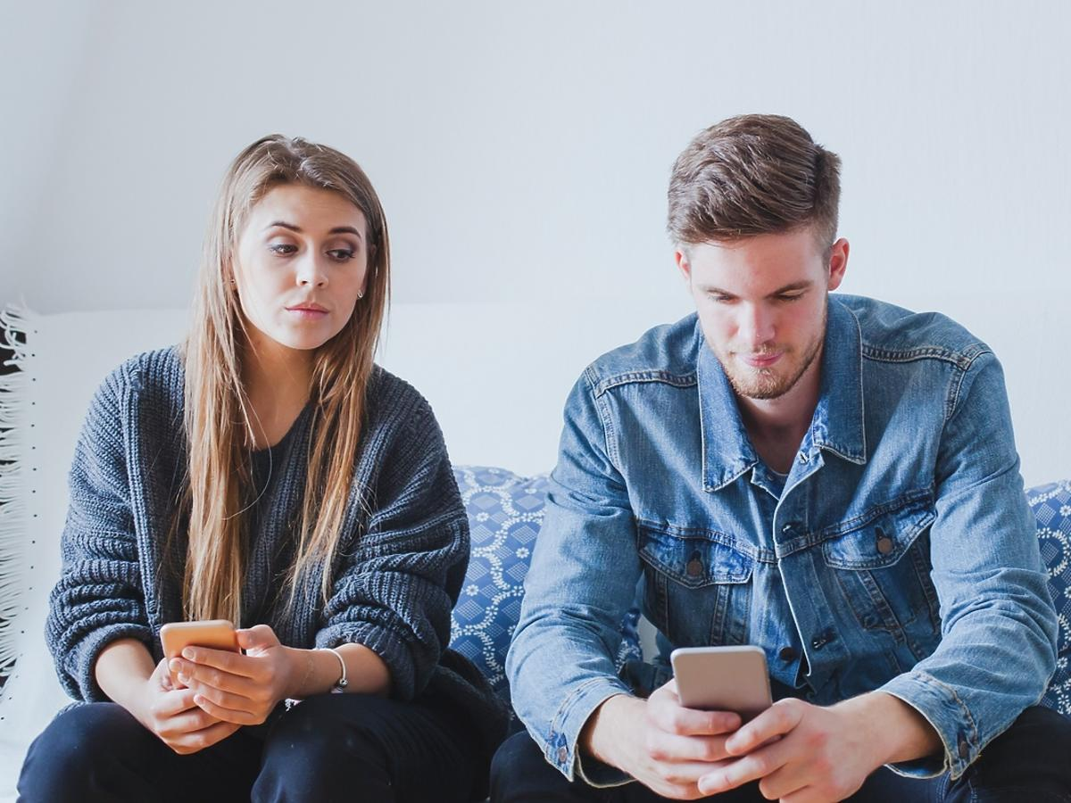 Kobieta zagląda swojemu chłopakowi przez ramię, który pisze smsy.