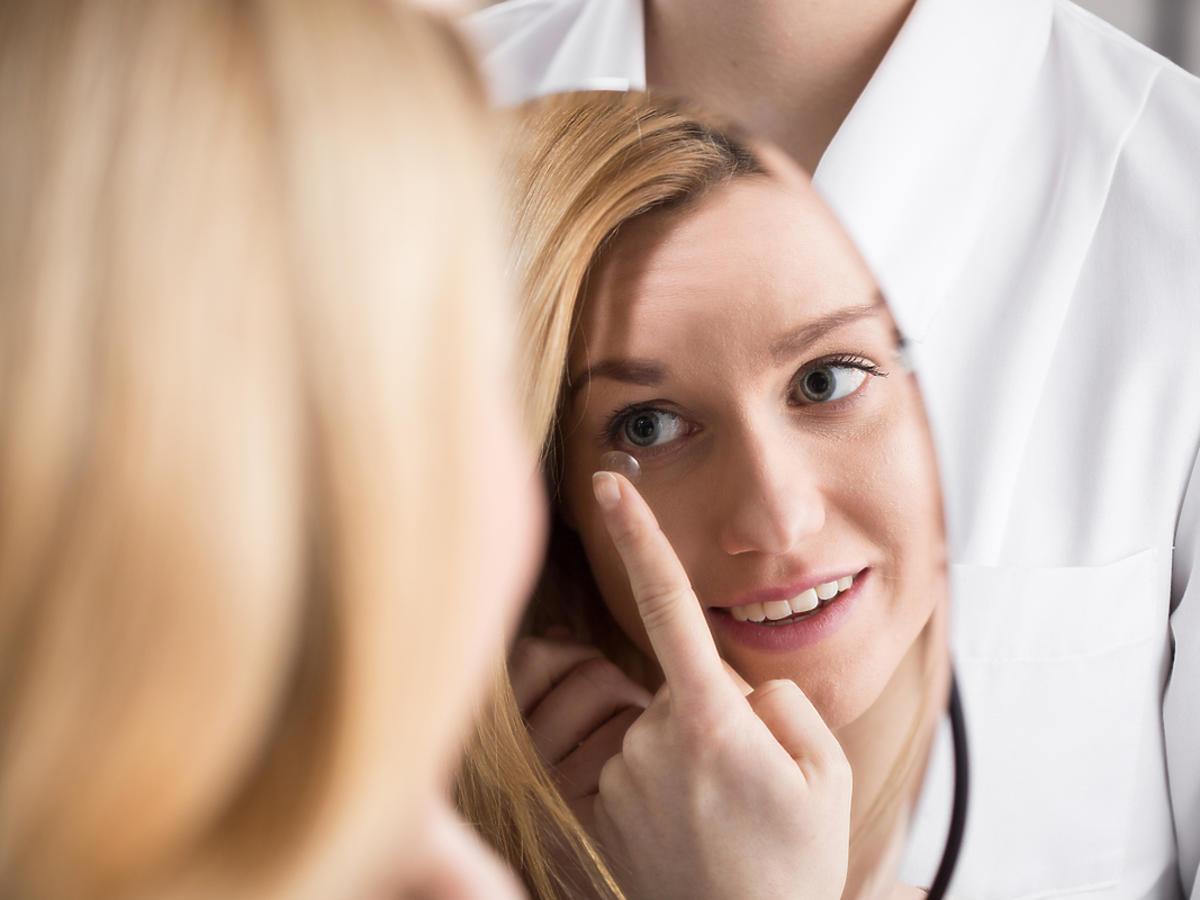 Kobieta zakłada sobie soczewkę kontaktową przed lusterkiem