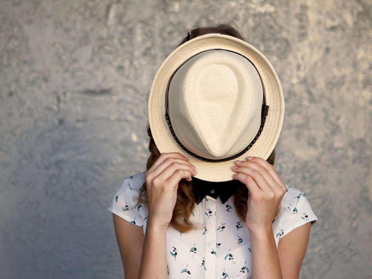 Kobieta zakrywa twarz kapeluszem