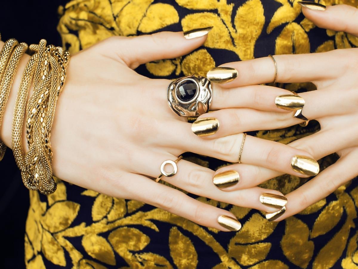 kobieta ze złotymi paznokciami i złotą biżuterią