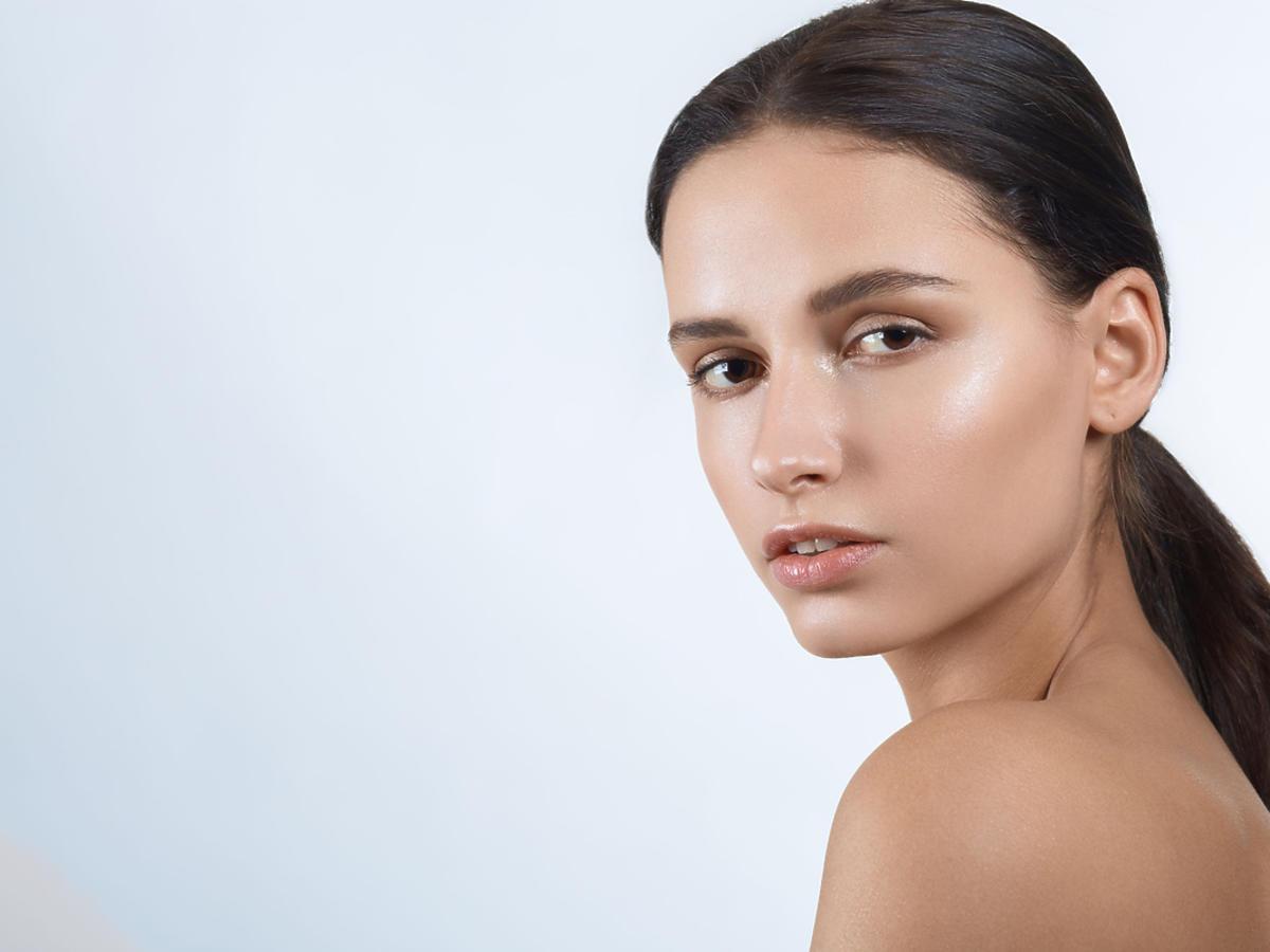 Kobieta ze związanymi włosami i zadbanymi, lecz bujnymi brwiami
