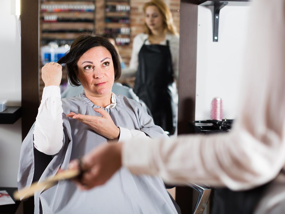 Kobieta znajduje się w salonie fryzjerskim i jest niezadowolona ze swojej fryzury.