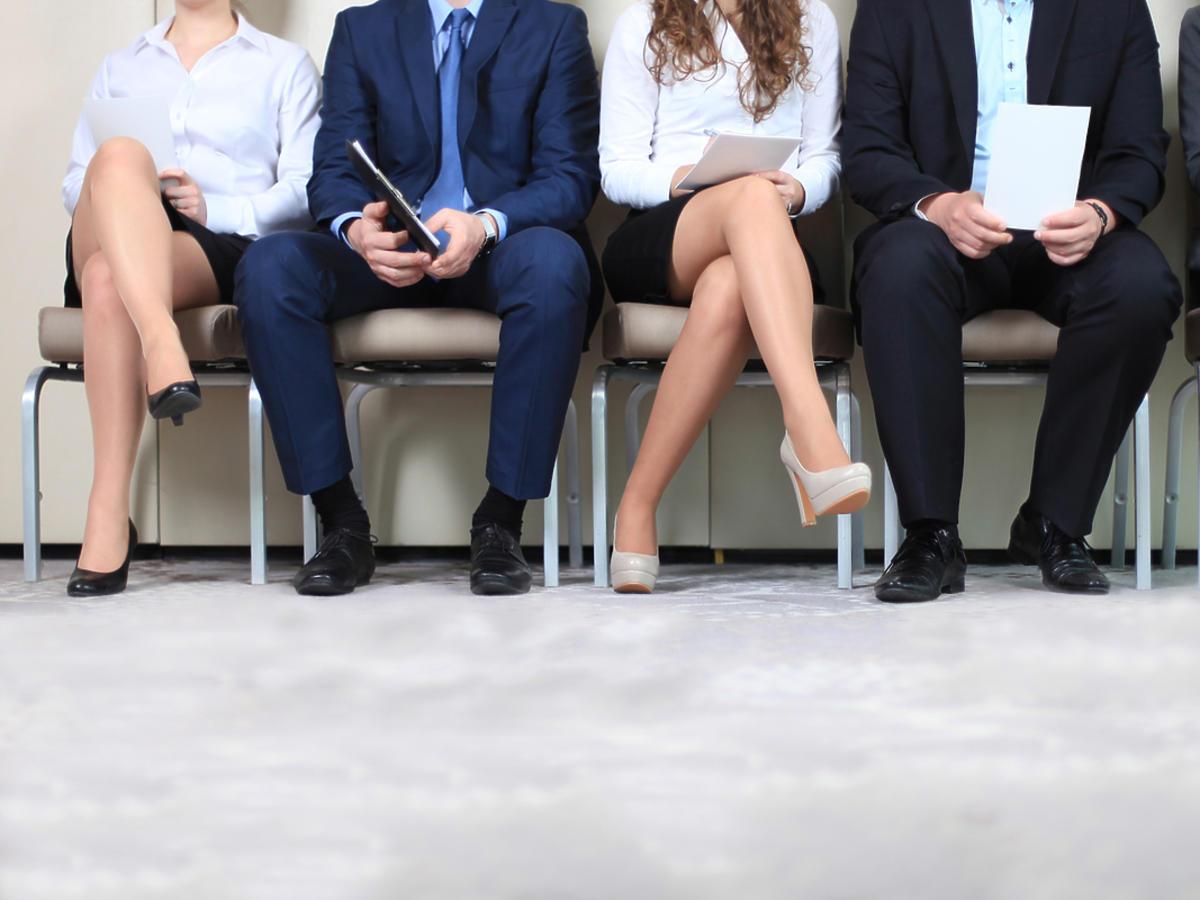 Kobiety i mężczyźni czekają na rozmowę kwalifikacyjną.