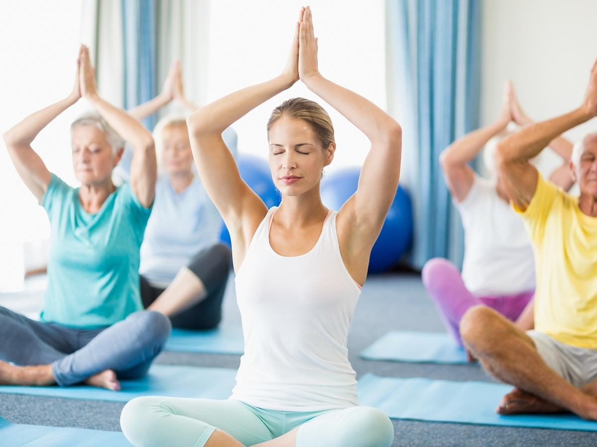 kobiety i mężczyzni w strojach sportowych na zajęciach jogi