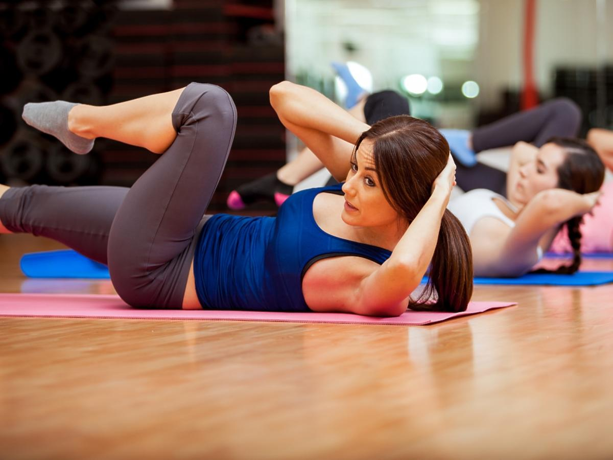 Kobiety leżą na podłodze i ćwiczą.