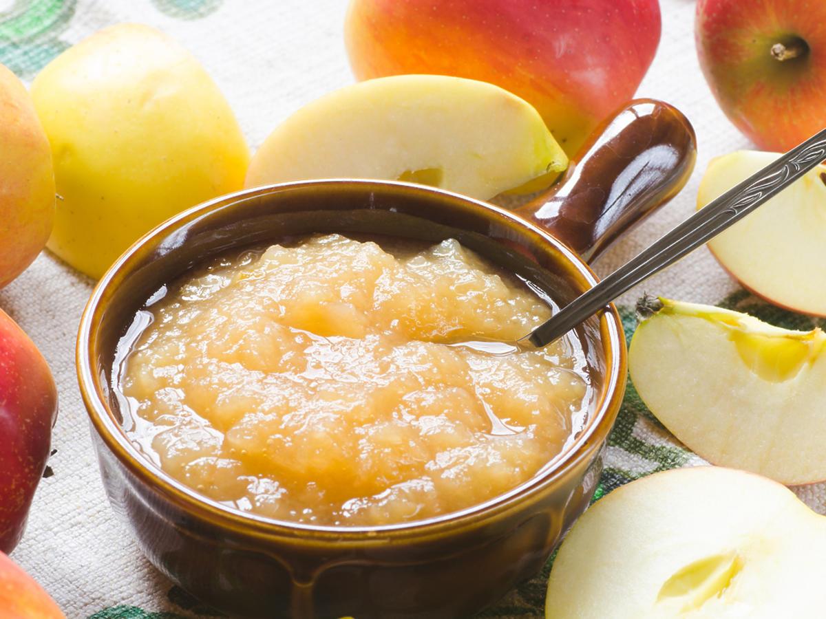 Konfitura z jabłek otoczona świeżymi jabłkami.