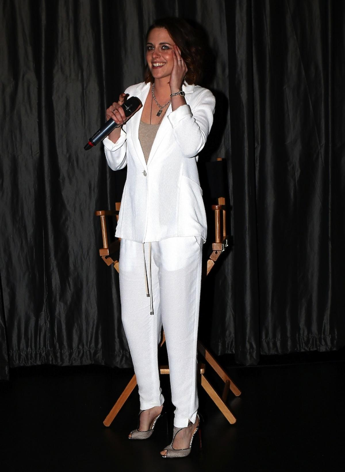 Kristen Stewart w białym garniturze przy mikrofonie