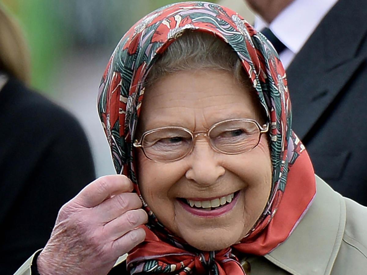 Królowa Elżbieta II, uśmiechnięta w chustce na głowie