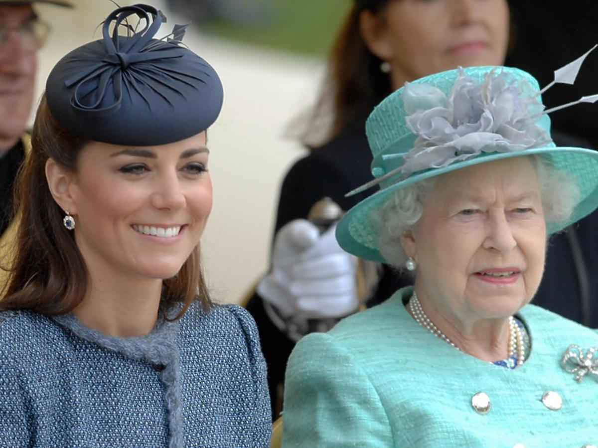 Księżna Kate w toczku i Elżbieta II w kapeluszu oglądają razem przedstawienie