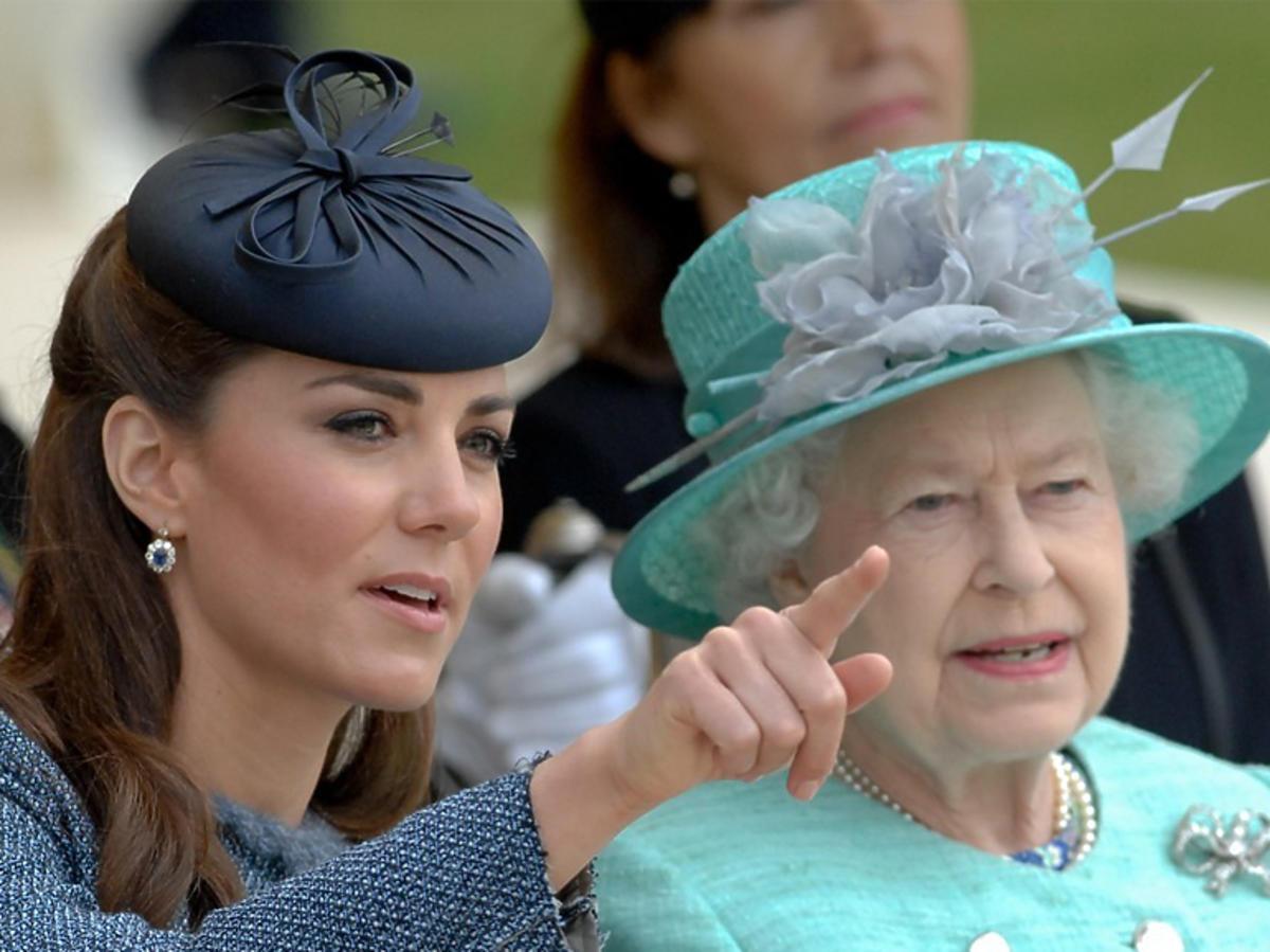 Księżna Kate w toczku i Elżbieta II w miętowej stylizacji oglądają razem przedstawienie