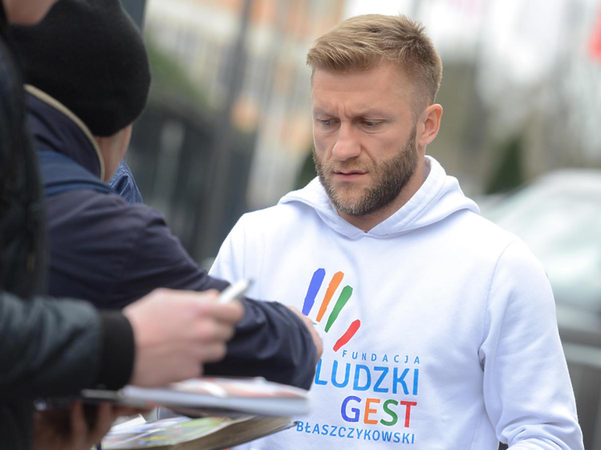 Kuba Błaszczykowski w bluzie swojej fundacji rozdaje autografy