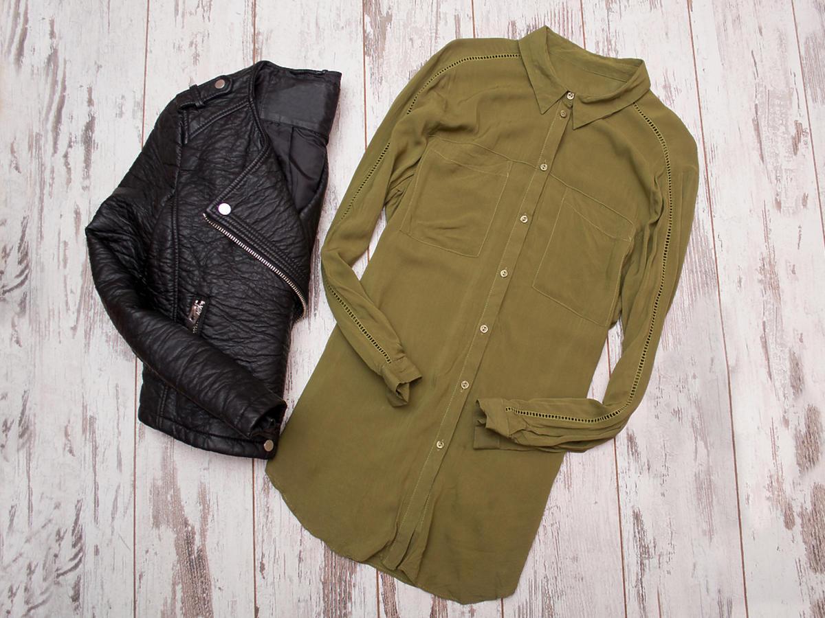Kurtki i bluzki w kolorze khaki leżą na podłodze.