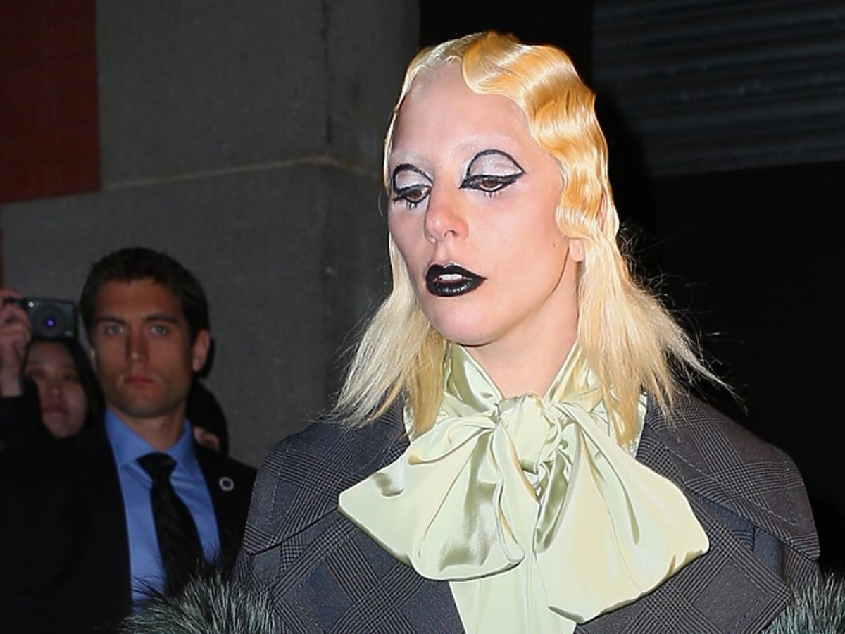 Lady Gaga w białej bluzce z żabotem i dziwnej pofalowanej fryzurze