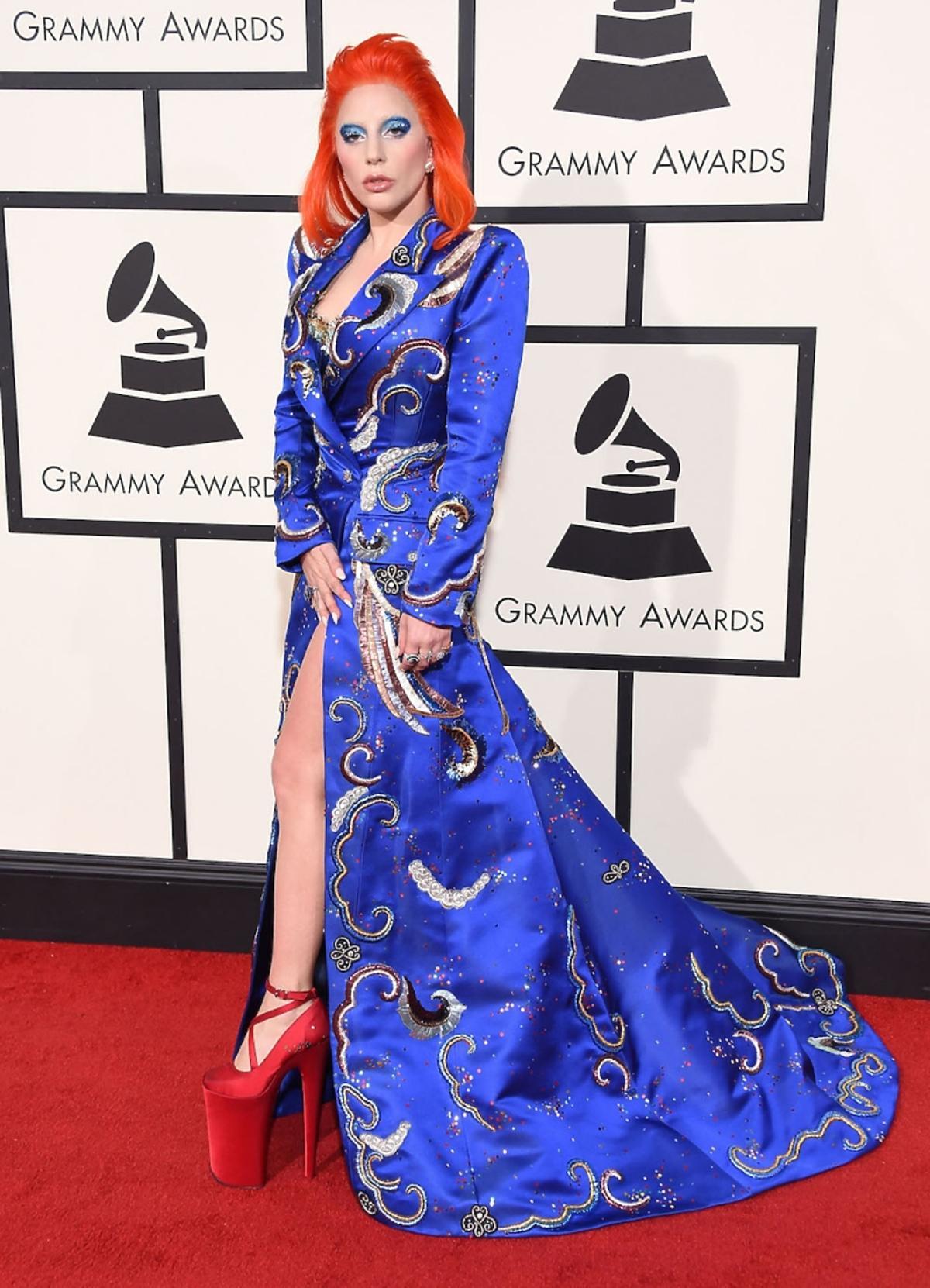 Lady Gaga w niebieskim płaszczu we wzory, czarwonych butach na koturnie i wysokiej szpilce