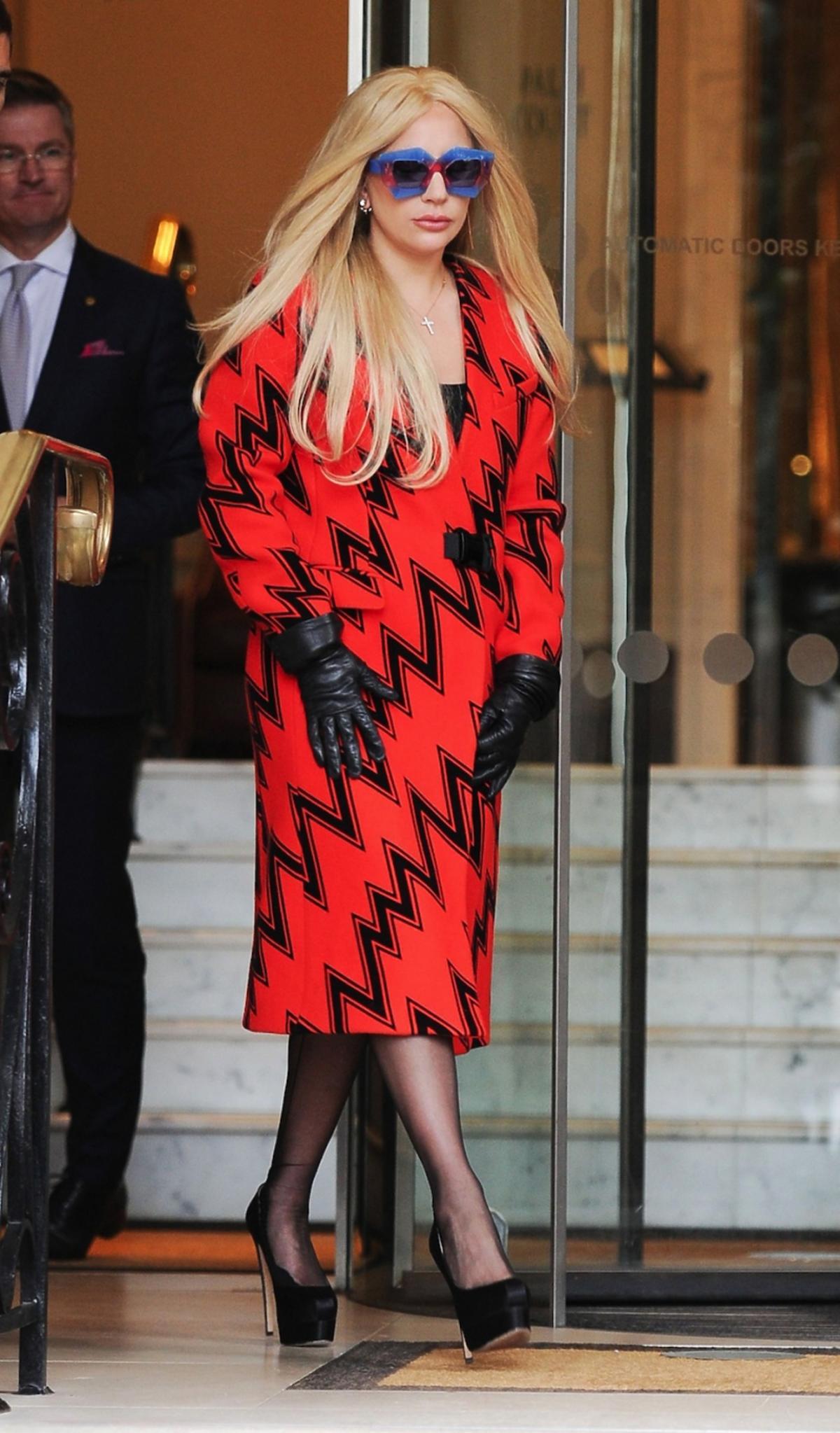 Lady Gaga w pomarańczowym płaszczu z nadrukiem w czarne zygzaki i rękawiczkach