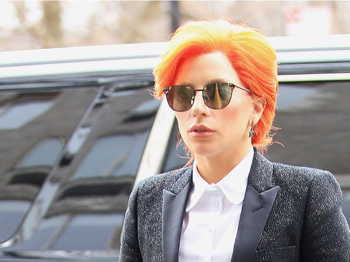 Lady Gaga w rudych włosach, ciemnych okularach i czarnym garniturze