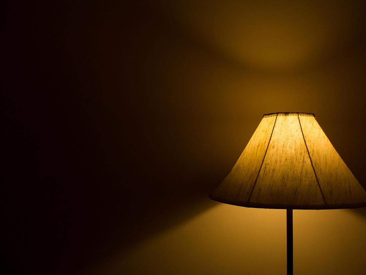 Lampa z abażurem świeci w ciemności.