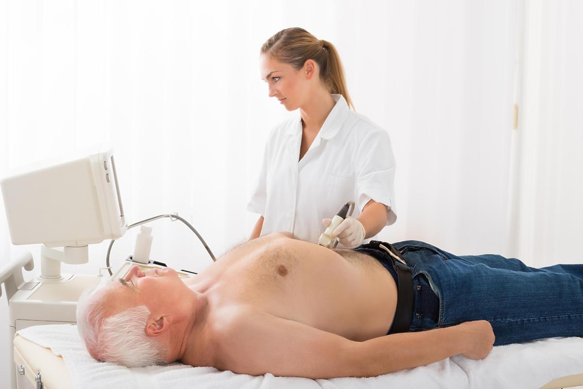 lekarka wykonuje badanie USG brzucha starszemu mężczyźnie